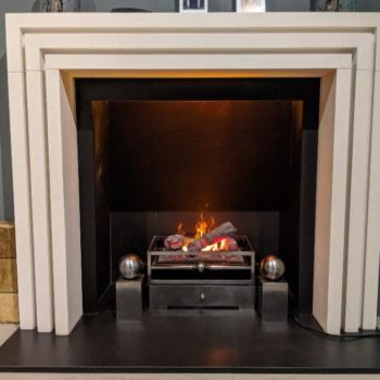 Chesneys Beckett fireplace by Kelly Hoppen with the Olympus electric fire, Byron fire basket for dogs and Spherical Steel fire dogs in showroom