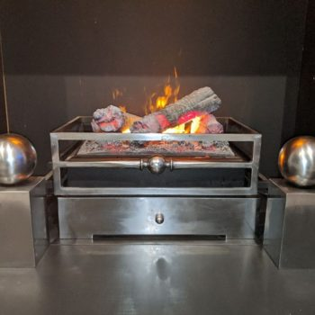 Chesneys Olympus electric fire, Byron fire basket for dogs and Spherical Steel fire dogs in showroom