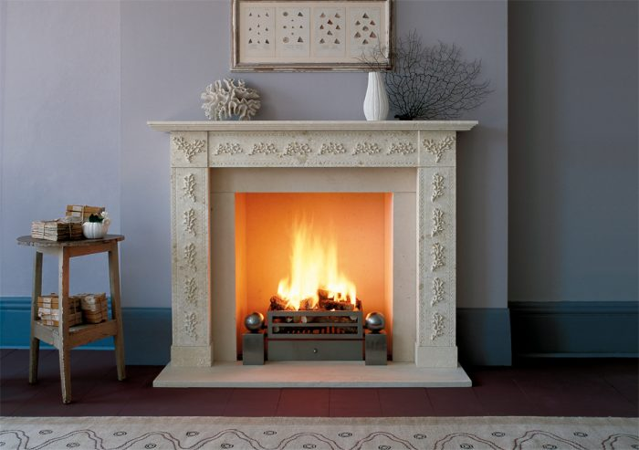 Chesneys Coral fireplace by Jane Churchill with Soho fire basket for dogs and Spherical Steel fire dogs