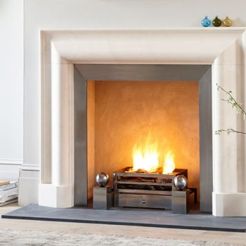Chesneys Kent Bolection fireplace with the Soho fire basket for dogs and Spherical steel fire dogs